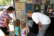 Beth Sedlock of Columbus (right) shows vistors how featured artist Mozart Dane creates the artwork for sale at the Harlequin Haven Great Dane Rescue booth during Art on the Lawn, the 28th Annual Fine Arts & Crafts Festival at Mills Lawn Elementary School in Yellow Springs, Saturday, August 13, 2011.  She explained that Mozart only paints at the shelter, and only when he feels like it.  Some days she said, Mozart will decide not to paint because he doesn't like the colors chosen for him.