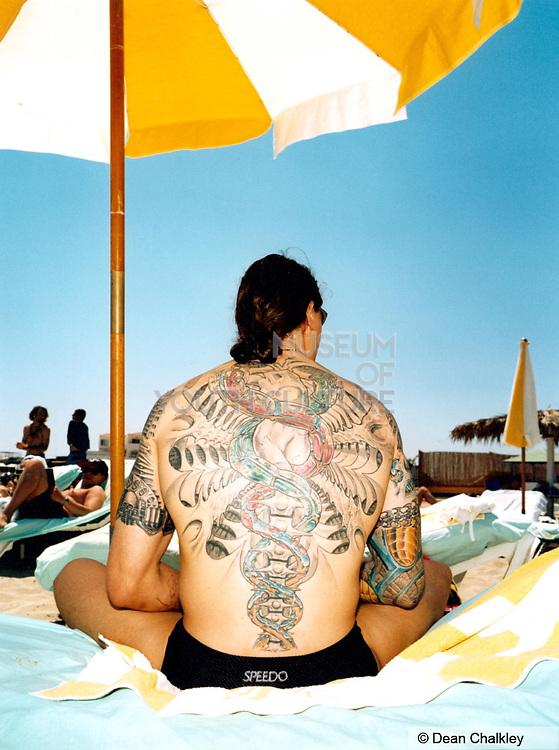 Tattoo man wearing speedos sitting under a sun umbrella on the beach Ibiza 1999