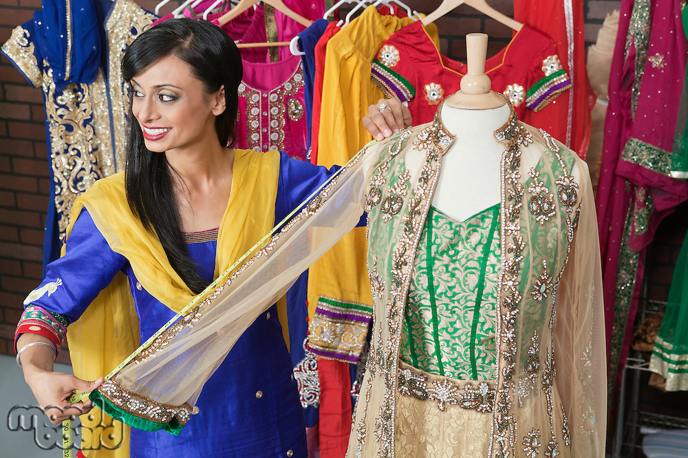 Indian female dressmaker measuring traditional outfit at design studio