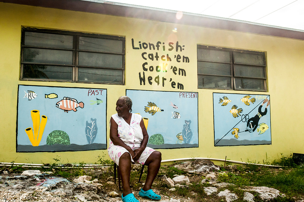 A mural is painted on the side of a small grocery store on Eleuthera Island, Bahamas depicting how the fait of the Bahamian fishery is tied closely to that of the invasive lionfish. An island elder looks to the past as a healthy fishery becomes embattled.