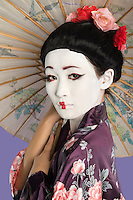 Close-up of Japanese woman with painted face holding parasol against purple background