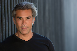 portrait of an Asian American man with gray hair and green eyes