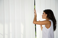 Woman looking trough curtains