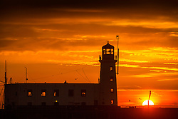 © Licensed to London News Pictures. 12/02/2019. Scarborough UK. The sun rises behind the Diving Bell statue next to Scarborough lighthouse this morning on the Yorkshire coast. Photo credit: Andrew McCaren/LNP