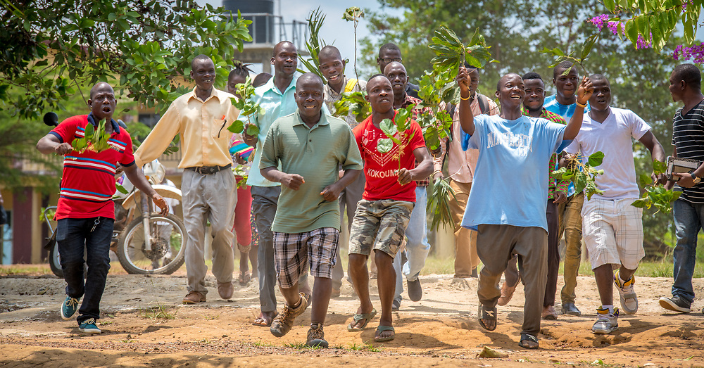 A group of people wave palms in celebration in Ganta,Liberia