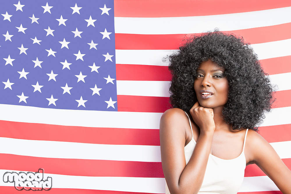 Portrait of stylish young woman with fizzy hairstyle standing against American flag