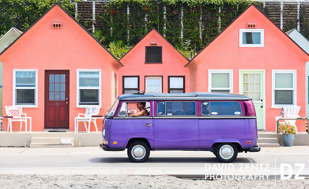 A purple VW Bus drives in front of Roberts Cottages in Oceanside, Calif., on Aug. 3, 2014.