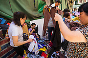 12 AUGUST 2013 - MACAU:  Shoppers look at used clothes for sale in a Macau market. Macau, also spelled Macao, is one of the two special administrative regions of the People's Republic of China (PRC), the other being Hong Kong. Macau lies on the western side of the Pearl River Delta across from Hong Kong to the east, bordered by Guangdong province to the north and facing the South China Sea to the east and south. The territory's economy is heavily dependent on gambling and tourism, but also includes manufacturing.     PHOTO BY JACK KURTZ