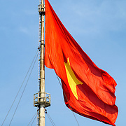 A large Vietnamese flag flies at the Imperial City in Hue, Vietnam. A self-enclosed and fortified palace, the complex includes the Purple Forbidden City, which was the inner sanctum of the imperial household, as well as temples, courtyards, gardens, and other buildings. Much of the Imperial City was damaged or destroyed during the Vietnam War. It is now designated as a UNESCO World Heritage site.