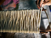 "29 DECEMBER 2018 - BANGKOK, THAILAND: Longevity noodles wrapped on wooden sticks before starting the drying process in a family shophouse. From here the noodles will go into a drying cabinet for two hours before being stretched and dried in the sun for three hours. The family has been making traditional ""mee sua"" noodles, also called ""longevity noodles"" for three generations in their home in central Bangkok. They use a recipe brought to Thailand from China. Longevity noodles are thought to contribute to a long and healthy life and  are served on special occasions, especially Chinese New Year, which is February 4, 2019. These noodles were being made for Chinese New Year.       PHOTO BY JACK KURTZ"