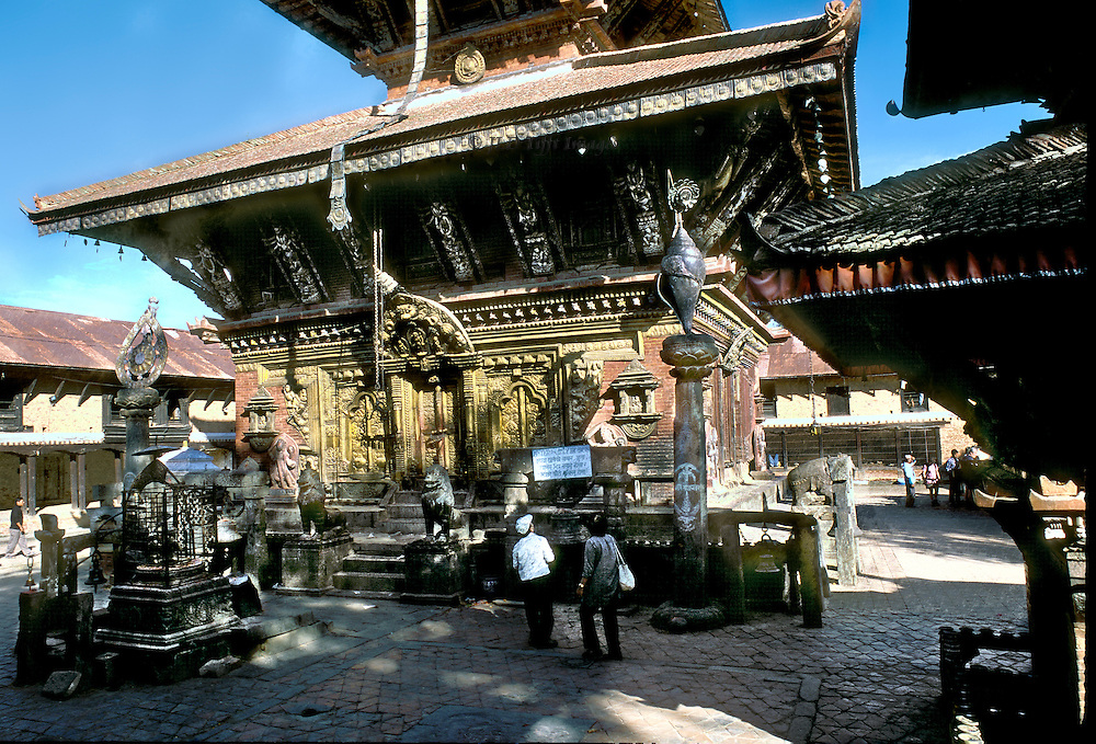Changu Narayan temple precinct; a World Heritage site, Kathmandu valley.  Temple dedicated to Chakra Narayan, traditionally built in 5th century and so the oldest temple in Kathmandu valley. Scattering of tourists study the structure.  The area is crowded with statuary and other sacred structures as well as living quarters of the caretakers.