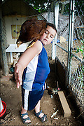 Boy with bird in chicken coop