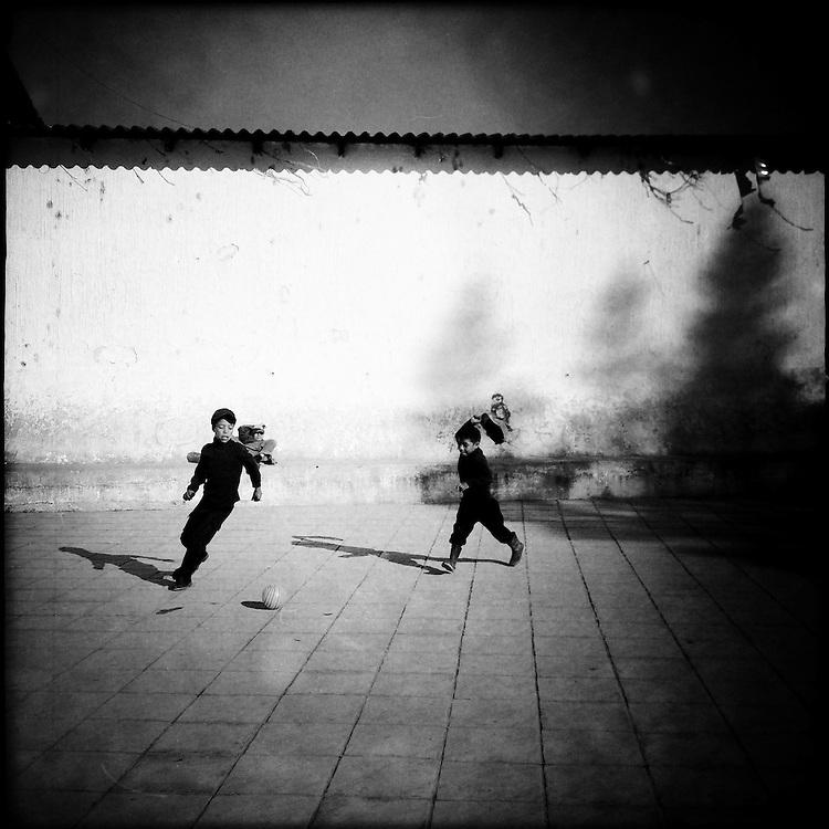 Children playing football, or soccer, in Nebaj's central park. Nebaj, Quiche, Guatemala. April 5, 2014.