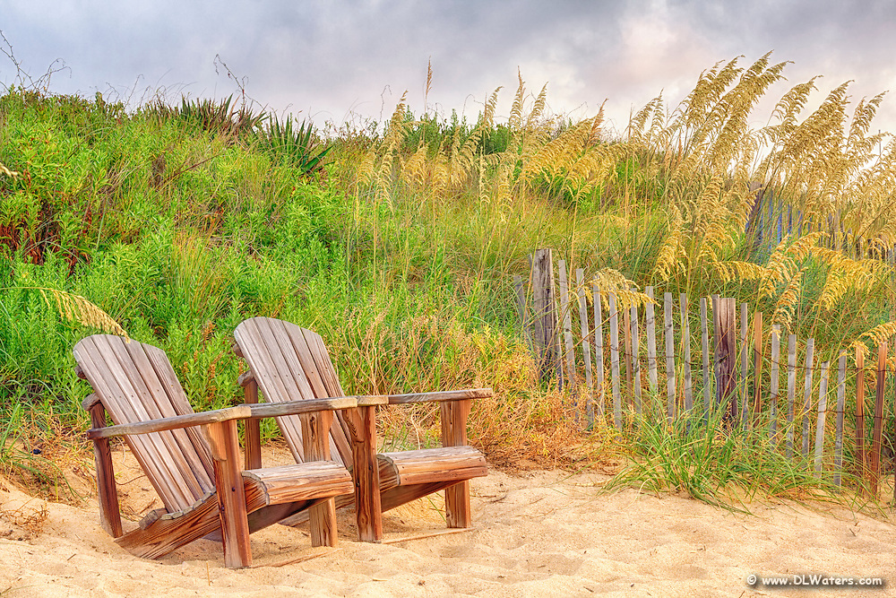 Side-by-side Adirondack chairs on the dunes in Kitty Hawk North Carolina.