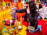 "29 APRIL 2017 - MINNEAPOLIS, MINNESOTA: A woman prays and bathes a statue of the Buddha at Songkran Uptown. Several thousand people attended Songkran Uptown on Hennepin Ave in Minneapolis for the city's first celebration of Songkran, the traditional Thai New Year. Events included a Thai parade, a performance of the Ramakien (the Thai version of the Indian Ramayana), a ""Ladyboy"" (drag queen) show, and Thai street food.     PHOTO BY JACK KURTZ"