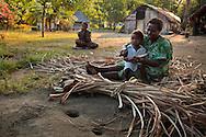 Ni Vanuatu woman weaving mats, with her child on her lap. Uleveo, Maskelyne Island, Malampa Province, Malekula, Vanuatu