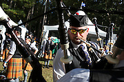 Derek Midgley of the Atlanta Pipe Band, helps tune another member of the band's bagpipes prior to their performance in the Highland Games at Stone Mountain Park on Saturday in Stone Mountain. (Staff Photo: David Welker)