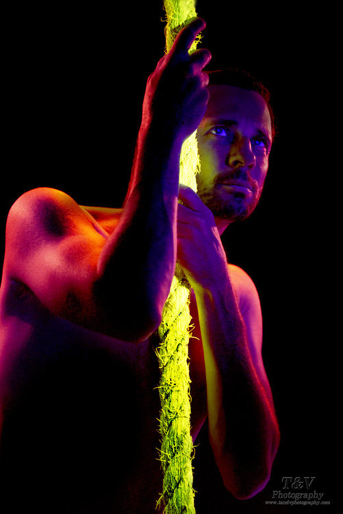 Man hanging on to glowing rope.Black light