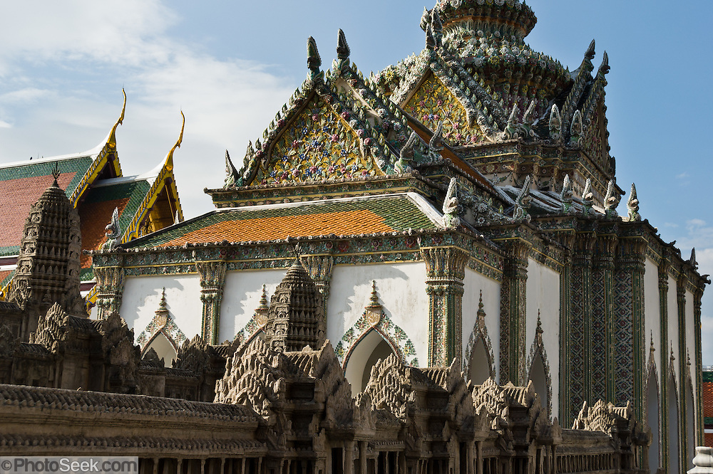 A brownish gray model of Angkor Wat (original is in Cambodia) rises in the Temple of the Emerald Buddha (Wat Phra Kaew), a shining complex of buildings within the grounds of the Grand Palace in Bangkok, Thailand. The Grand Palace complex (Phra Borom Maha Ratcha Wang) was built on the east bank of the Chao Phraya River starting in 1782, during the reign of Rama I. It served as the official residence of the king of Thailand from the 1700s to mid 1900s.