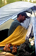 A camper in his tent on a rainy day in the mountains of Colorado