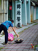 25 AUGUST 2018 - GEORGE TOWN, PENANG, MALAYSIA: A woman burns ghost money on the street on Ghost Day, the full moon day (or night) that falls in the middle of Hungry Ghost month. The Ghost Festival, also known as the Hungry Ghost Festival is a traditional Taoist and Buddhist festival held in Chinese communities throughout Asia. Ghost Day, is on the 15th night of the seventh month (25 August in 2018). During Ghost Festival, the deceased are believed to visit the living. In many Chinese communities, there are Chinese operas and puppet shows and elaborate banquets are staged to appease the ghosts.      PHOTO BY JACK KURTZ