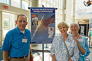 L-R, KEN MALONEY and SUE MALONEY of Houston Texas, and the couple's guest JOAN WEBER, who lives locally in Merrick, are in atrium lobby of Cradle of Aviation Museum for a reunion of former Northrop Grumman Aerospace Corporation employees during a Summer of '69 Celebration held on the 45th Anniversary of NASA Apollo 11 LEM landing on the moon July 20, 1969. Ken was a Lunar Excursion Module LEM spacecraft scheduler at Kennedy Space Center, Florida, for STM, spacecraft test management, and Sue was a secretary for avionics management in Bethpage and flight test at Calverton. They are standing next to a poster for an event that will be held there that evening with two Apollo astronauts, F. Haise and W. Cunningham.