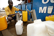 A man fills plastic containers with water from a tap in a poor neighborhood of Accra, Ghana's capital, on Monday Mar 5, 2007. Most parts of the city are plagued with intermittent water shortages, and people buy water from the few running taps. They then have to carry the containers to their homes over distances that often reach several hundred meters. Meanwhile, Ghana is preparing to celebrate its 50 years of independence from the UK on March 6th.