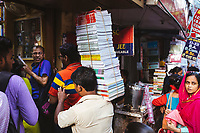 A man carries a stack of books to a second-hand bookstore near College Street in Kolkata.