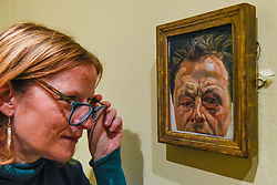 "© Licensed to London News Pictures. 23/10/2019. LONDON, UK. A staff member views ""Self-Portrait with a Black-Eye"", 1978, by Lucien Freud. Preview of ""Lucian Freud: The Self-portraits"" at the Royal Academy of Arts in Piccadilly.  56 works on display chart Freud's artistic development over almost seven decades on canvas and paper in a show which runs 27 October to 26 January 2020.  Photo credit: Stephen Chung/LNP"