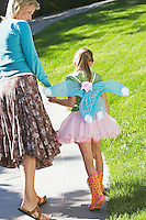Girl wearing fairy wings and tutu walking with mother on park path back view