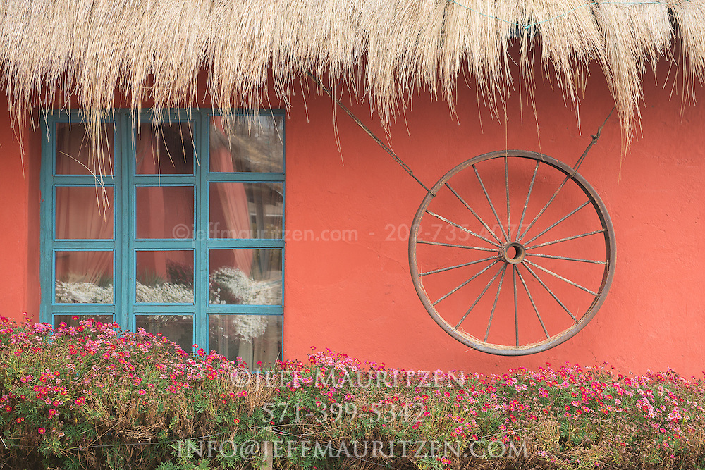 A wheel hangs outside a thatched hacienda in the Andes of Ecuador.