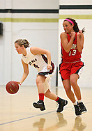 Davenport Assumption's Danielle Moore (13) tries to avoid a foul as Linn-Mar's Mykaela Brandt (4) brings the ball down court during the 2013 Eastern Iowa All-Star Basketball Game at Iowa City West High School in Iowa City on Wednesday, March 27, 2013. The North (white) defeated the South (dark) 68-65.