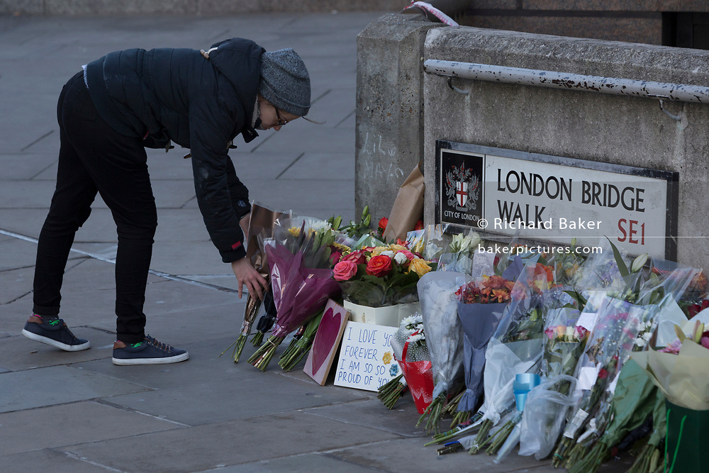 Three days after the killing of Jack Merritt, 25, and Saskia Jones, 23, by the convicted teorrorist Usman Khan at Fishmongers' Hall on London Bridge, a memorial of flowers appeared at the southern (Southwark) end of the bridge where passers-by and commuters walk on their way to work in the City at the opposite side of the river Thames, in the City of London, on 2nd December 2019, in London, England.