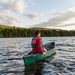 A man paddles his canoe on Long Pond in Maine's north woods. Near Greenville, Maine.