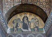 Detail of Deesis mosaic, late 10th century, showing Emperor Justinian, 483-565, offering the Hagia Sophia, and Emperor Constantine, offering Constantinople, to the Virgin and Christ Child, in the vestibule of Haghia Sophia, 532-37, by Isidore of Miletus and Anthemius of Tralles, Istanbul, Turkey. Hagia Sophia, The Church of the Holy Wisdom, has been a  Byzantine church and an Ottoman mosque and is now a museum. The current building, the third on the site, commissioned by Justinian I, is a very fine example of Byzantine architecture. The historical areas of the city were declared a UNESCO World Heritage Site in 1985. Picture by Manuel Cohen.