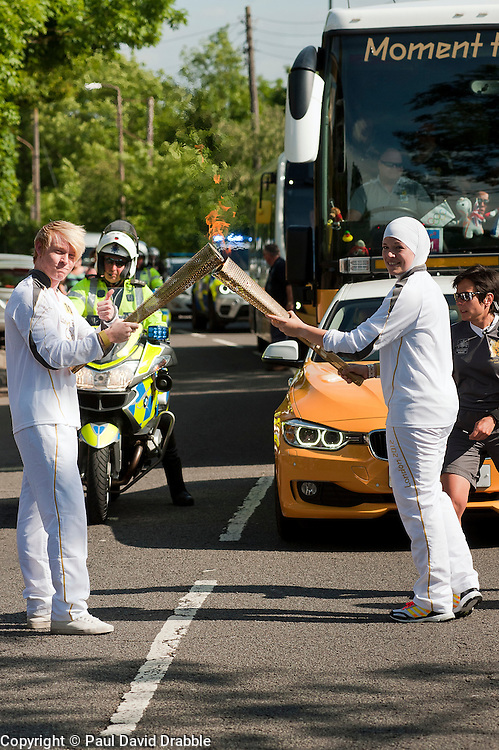 Olympic Torch reaches Sheffield Chapeltown/Ecclesfield/Parson Cross leg.<br /> Handover runner 101 Dana Abdulkarim (right) hands the flame on to Joshua McGill runner 102<br /> 25 June 2012.Image &copy; Paul David Drabble