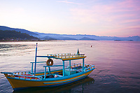 colorful boat at sunset in the bay of beautiful portuguese colonial typical town of parati in rio de janeiro state brazil