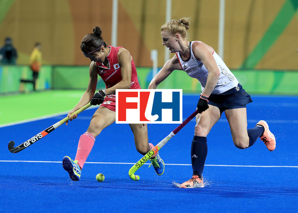 RIO DE JANEIRO, BRAZIL - AUGUST 11:  Miyuki Nakagawa #5 of Japan is defended by Nicola White #28 of Great Britain during a Women's Preliminary Pool B match at the Olympic Hockey Centre on August 11, 2016 in Rio de Janeiro, Brazil.  (Photo by Sam Greenwood/Getty Images)