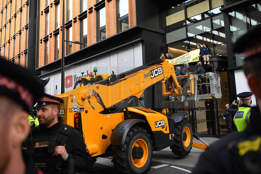 © Licensed to London News Pictures. 16/10/2019. London, UK. A JCB aerial platform is brought in to deal with young Extinction Rebellion activists (XR Youth) blocking the entrance to Google owned Youtube in Kings Cross London, calling for accurate representation on climate change on their platform. Photo credit: Guilhem Baker/LNP