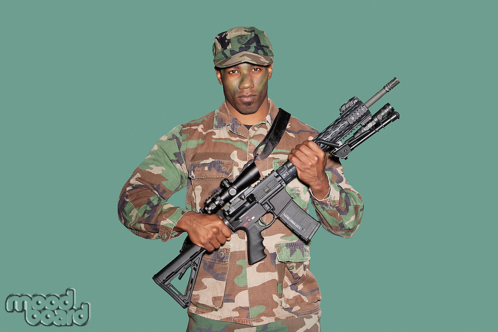 Portrait of a young African American US Marine Corps soldier with M4 assault rifle over green background