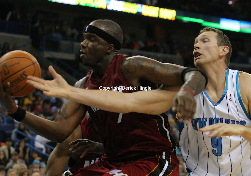 Dec 30, 2009; New Orleans, LA, USA;  New Orleans Hornets forward Darius Songaila (9) reaches in as Miami Heat center Jermaine O'Neal (7) tries to gain control of the ball during the second half at the New Orleans Arena. The Hornets defeated the Heat 95-91. Mandatory Credit: Derick E. Hingle-US PRESSWIRE
