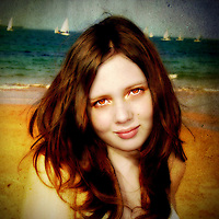 A young woman at the beach looking directly at the camera with sailing boats in the background