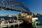 Ferry at Milsons Point wharf, with Sydney Harbour Bridge in background. Sydney, Australia