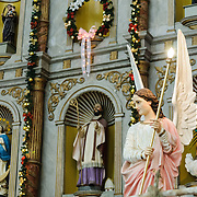 A statue of an angel in the foreground, with the main altar of the Cathedral of San Gervasio (Catedral De San Gervasio) in the background. This is the main church in Valladolid in the heart of Mexico's Yucatan Peninsula.