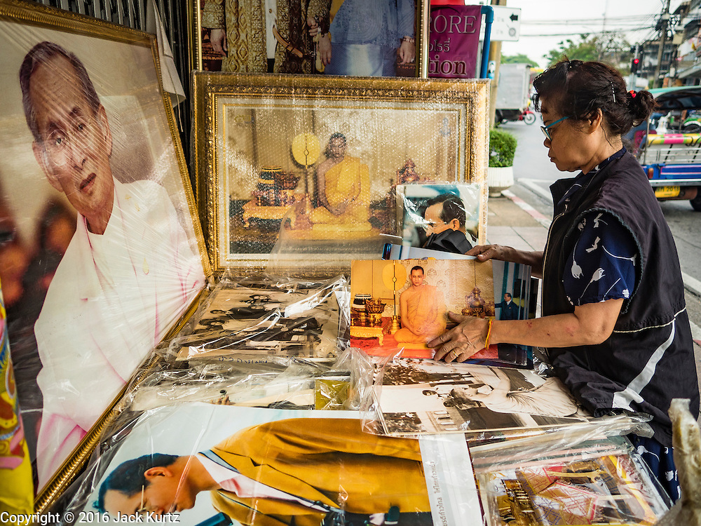 18 OCTOBER 2016 - BANGKOK, THAILAND: A shopkeeper sets up a display of portraits of Bhumibol Adulyadej, the late King of Thailand, in front of her shop. The King died Oct. 13, 2016. He was 88. His death came after a period of failing health. Bhumibol Adulyadej was born in Cambridge, MA, on 5 December 1927. He was the ninth monarch of Thailand from the Chakri Dynasty and is also known as Rama IX. He became King on June 9, 1946 and served as King of Thailand for 70 years, 126 days. He was, at the time of his death, the world's longest-serving head of state and the longest-reigning monarch in Thai history.     PHOTO BY JACK KURTZ