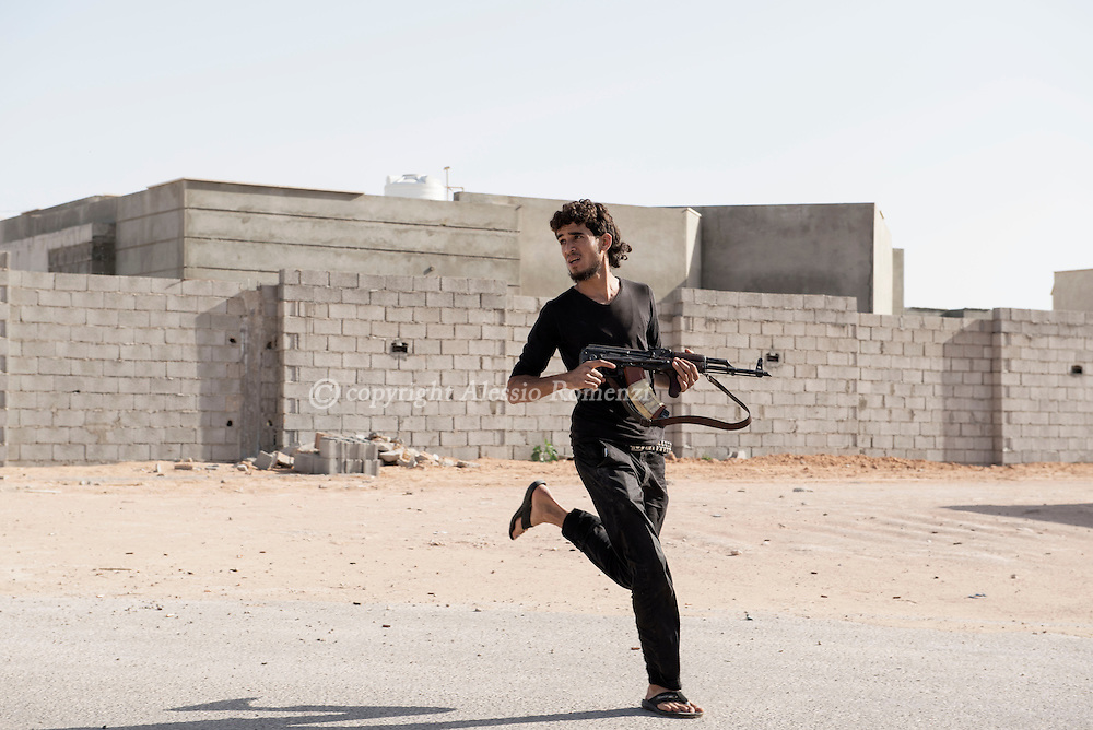 Libya: to avoid ISIS sniper fire a fighter affiliated with Libya's Government of National Accord's (GNA) runs to cross a road in 700 neighbourhood in Sirte still under ISIS control. Alessio Romenzi