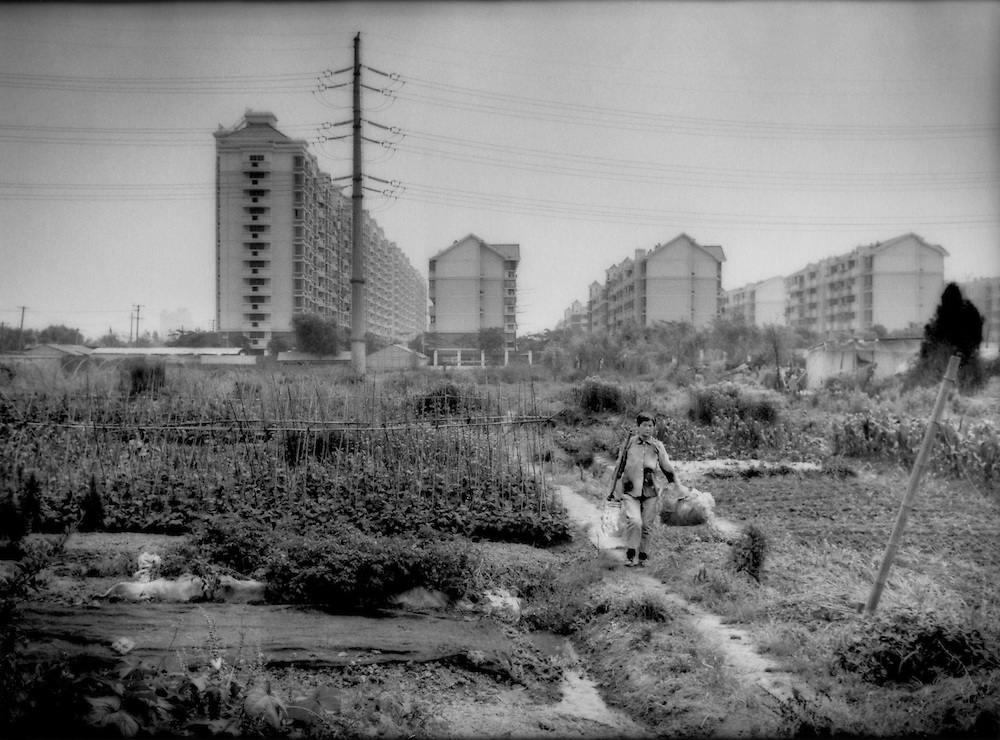 Woman farmer returns from her field overshadowed by new apartment complex as the edge of Shanghai swallows up her farming community, near Longyang Station, Pudong, Shanghai, China.