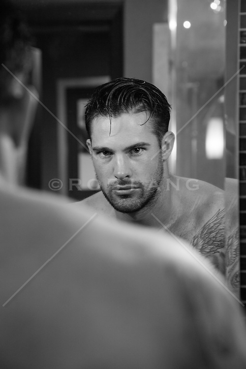 shirtless sexy man looking at himself in a mirror