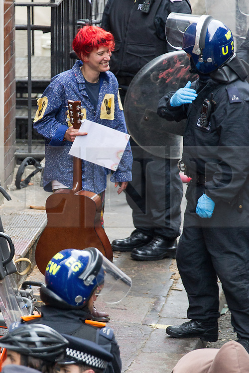 © Licensed to London News Pictures . 11/06/2013 . London , UK . Police lead away a person with a guitar from inside after cutting their way in with an angle grinder . Police surround a former police station on 40 Beak Street , Soho this morning (11th June) . The site has been occupied by organisers of today's Stop G8 anti capitalist protests . Demonstrations in London today (Tuesday 11th June 2013) ahead of Britain hosting the 39th G8 summit on 17th/18th June at the Lough Erne Resort , County Fermanagh , Northern Ireland , next week . Photo credit : Joel Goodman/LNP