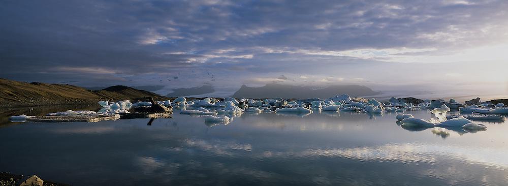 Europe, Iceland, Setting midnight sun lights icebergs from Bre?amerkursandur Glacier in Jökulsarlon lagoon